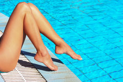 Female legs at blue water of swimming pool Stock Photography