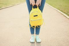 Female legs with bright fashionable yellow backpack stock photos