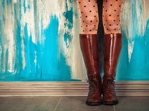 Female legs in brown leather boots near the wall. Female legs in high brown leather boots near the wall Stock Images