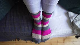 Female legs in brown-pink warm knitted socks close-up on a cozy sofa with a blanket. Life philosophy of Lagom, the