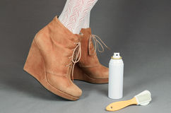 Female legs in brown suede boots on a gray background. Cleaning Stock Photo