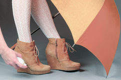 Female legs in brown suede boots under an umbrella on a gray bac Royalty Free Stock Photo