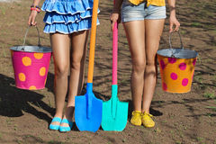 Female legs with buckets and shovels Stock Photo
