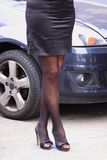 Female legs and car in town Royalty Free Stock Images