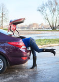 Female legs from car trunk. Woman body into car luggage trunk. Legs sticking out Royalty Free Stock Image