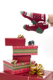 Female legs in christmas stockings against white. Female legs in christmas stockings isolated on white. Gifts on the floor Royalty Free Stock Photos