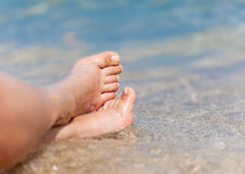 Female legs close-up on the beach in the water. Legs of woman close-up on the beach in the water Royalty Free Stock Image