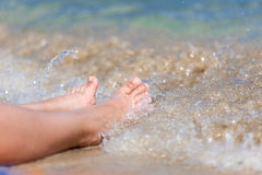 Female legs close-up on the beach in the water. Legs of woman close-up on the beach in the water Royalty Free Stock Photography