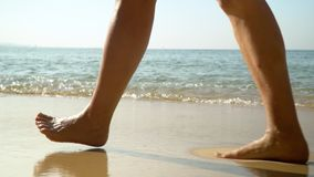 Female legs close up. The happy woman goes near ocean waves. Ocean surf. Tropical island. Slow mothion.. On this video you can see as the woman in a red dress stock video footage