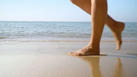 Female legs close up. Woman feet and legs walking on beach.Ocean surf. Tropical island. Slow mothion.. On this video you can see as the woman in a red dress stock footage
