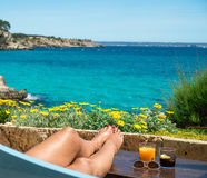 Female legs and cocktails against a tropical sea and flowers. Woman relaxing with some drinks. View towards tropical turquoise sea with yellow flowers and blue Royalty Free Stock Photo