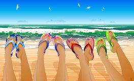 Female legs in colored flip flops. Against the sunny beach Royalty Free Stock Image