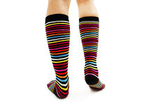 Female legs in colorful striped socks from the back. Isolated on white background Royalty Free Stock Images