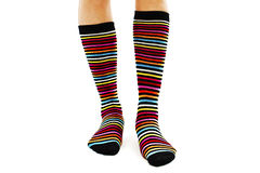 Female legs in colorful striped socks. Isolated on white background Royalty Free Stock Image