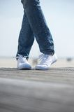 Female legs in comfortable white shoes standing outdoors Stock Photography