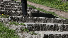 Female legs coming up the stone stairs in a city park stock video footage