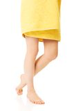 Female legs covered with a yellow towel Stock Photo