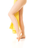 Female legs covered with a yellow towel Royalty Free Stock Photo