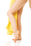 Female legs covered with a yellow towel Royalty Free Stock Images