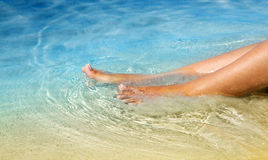 Female legs in the crystalline water Royalty Free Stock Image