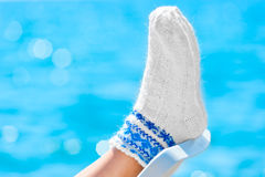 Female legs dressed in woolen socks on the beach Stock Photography