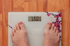 Female legs on the electronic scales, the scale shows 56 kg stock images