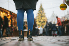 Female legs in fancy boots and tights against Christmas market Stock Photos