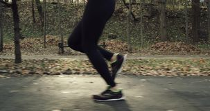 Female legs feet running in park road on morning. Woman running trail close up shoes dji ronin shot in 4k. Red Epic Slow stock footage