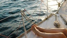 Female legs feet on the sailing yacht closeup in the open sea. Female legs feet on the sailing yacht closeup swings on the waves in the open sea stock photos
