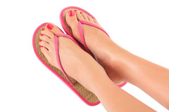 Female legs with flip-flops. Isolated on white background stock image
