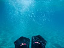 Female legs with flippers underwater view of the beautiful Skala beach of Kefalonia island, Ionian sea, Greece stock photography