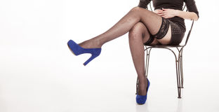 Female legs of girl sitting on a chair in black stockings Royalty Free Stock Images