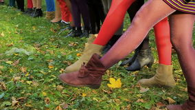 Female legs on grass. Tights of different colors on girls` legs. Girls raise up their legs in stockings stock video