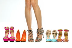 Female legs with a group of various high heels shoes;. Beautiful female legs wearing high heels shoes and standing next to other various high heels Stock Photos