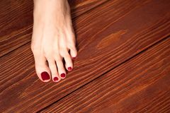 Female legs with hands with manicure and pedicure on the wooden floor. royalty free stock image