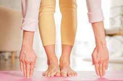 Female legs and hands. Woman doing yoga on the fitness mat at home stock photos