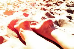 Female legs heels up on a sandy beach in a Sunny Tropical vacation concept of holiday and relaxation pekudei the sun. Tinted Stock Photography