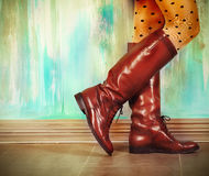 Female legs in high brown leather boots. Near the wall Stock Photos