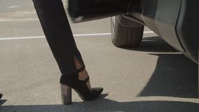 Female legs in high heel shoes getting into car. Close-up of slender female legs in stylish black high heels and pants getting into parked car. Low section of stock footage