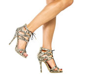 Female legs in High Heels Shoes with animal print design. Beautiful female legs in strappy high heels shoes with small platform sole and ankle straps, animal royalty free stock photo