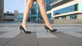 Female legs in high heels shoes walking in the urban street. Feet of young business woman in high-heeled footwear going Royalty Free Stock Images
