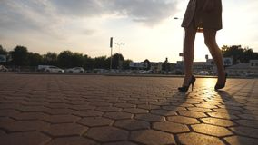 Female legs in high heels shoes walking in the urban street at sunset. Feet of young business woman in high-heeled. Footwear going in the city with sun flare at stock video footage