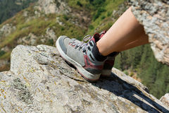 Female legs in hiking leather boots on a rocky mountain Stock Image
