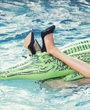 Female legs hold mattress in swimming pool. shoes from crocodile leather. woman on sea with inflatable mattress.Fashion royalty free stock images