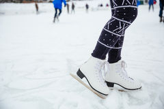 Female legs in ice skates. Closeup portrait of a female legs in ice skates Royalty Free Stock Photography