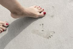 Female legs and imprint of the child`s footprint stock photography