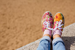Female legs in jeans and a bright floral sneakers in the backgro Royalty Free Stock Image