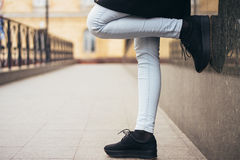 Female legs in jeans on the sidewalk while walking in the city Royalty Free Stock Image