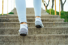 Female legs in jeans and sneakers, climb the concrete stairs out Stock Photos