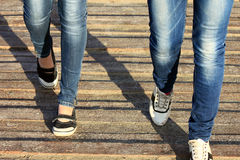 Female legs in jeans and sneakers closeup on wooden background Royalty Free Stock Images